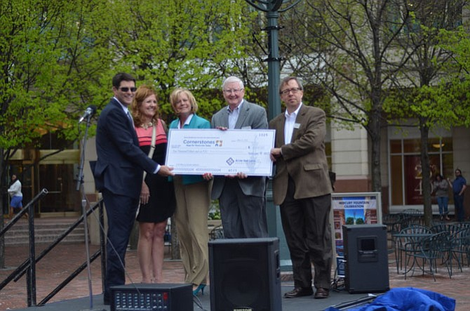 Reston Town Center Association executive director Robert Goudie (left) with representatives of the non-profit Cornerstones at Reston Town Center. All of the coins collected in the fountain in 2014 were donated to the organization Cornerstones.