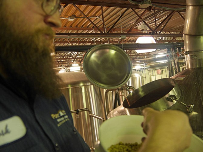 Josh Center, brewer at Port City Brewing Company in Alexandria, adds pellets of dry hops to the whirlpool kettle. Different combinations of hops are added to the kettles at different stages of brewing depending on the particular beer.