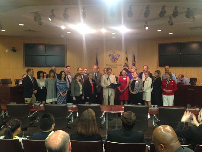 Montgomery County Council Member Roger Berliner (center) reads a proclamation saluting small business owners during a County Council meeting