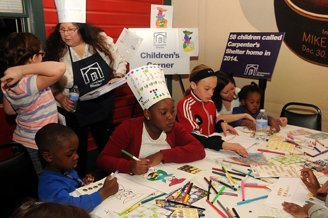 Children busy themselves coloring and decorating chefs hats in the children's craft corner.