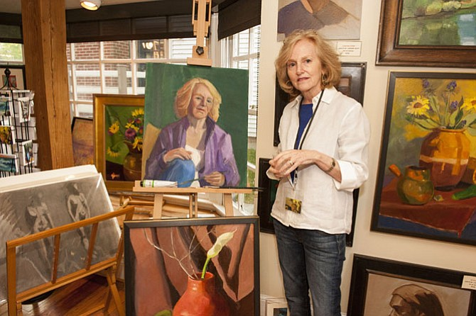 Painter Judith St. Ledger-Roty alongside a self-portrait, a nearly finished work in progress.