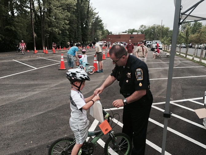 Public Information Officer Gary Lose chats with one of the children participating in the bike rodeo sponsored by the Town of Vienna Parks and Recreation department. Approximately 100 children participated in the four-hour event.