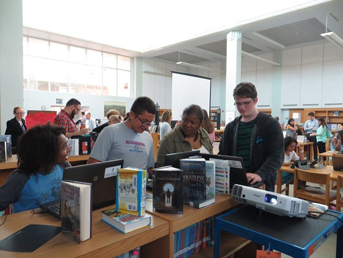 Emmanuel Teferra (left) discusses his progress in Minecraft with his teacher, Traci Holland-Shuford, while Joseph Gutierrez (center) and Owen Malone (right) play.