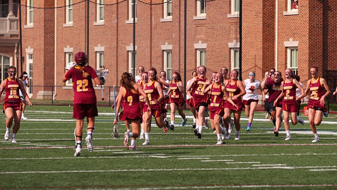 Members of the Bishop Ireton girls' lacrosse team celebrate the program's second consecutive state championship after defeating St. Stephen's & St. Agnes 12-10 on May 16 at Randolph-Macon College.