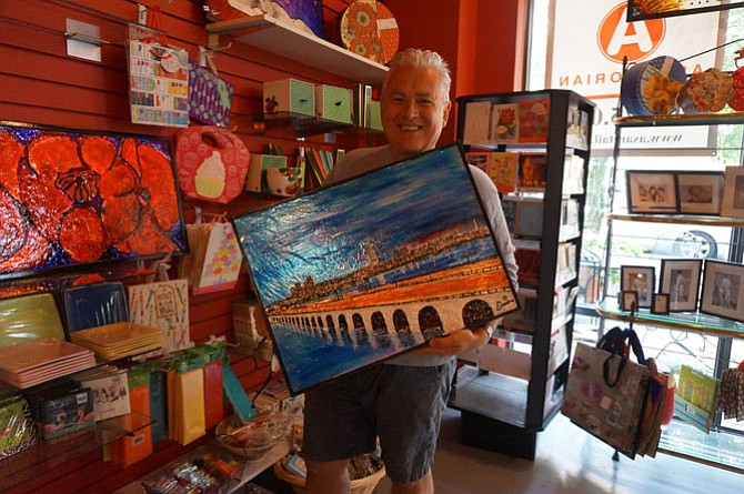 Artist Eric Nelson holds an original piece depicting the skyline of Alexandria from across the Woodrow Wilson Bridge. After five years in the Carlyle area, the Artfully Chocolate Bistro owner will be closing his doors May 27 and selling dozens of his original works through Alexandria-based online auction house Rasmus Auctions.