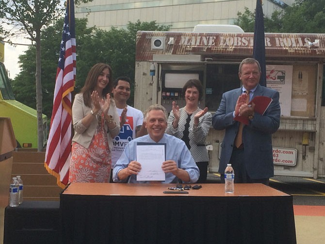 Rear from left, Del. Eileen Filler-Corn (D-41), Board of Supervisors chairman Sharon Bulova, Executive Director of the DMV Food Truck Association Che Ruddell-Tabisola and Jim Corcoran, President & CEO of the Fairfax County Chamber of Commerce applaud as Gov. Terry McAuliffe (D) signs a bill calling for regulations for food trucks to operate on specific roads in Virginia.