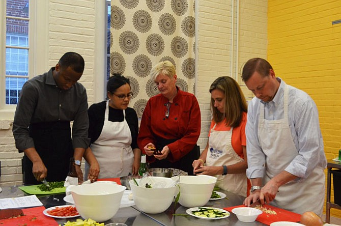 Knife skills are the first lessons taught in the kitchen at Date Night: Chef's Table at the Lorton Workhouse Arts center. From left: Andre and Rose Prince of Reston, Chef Kathleen Linton and Kara and Christian McCarty of Burke.