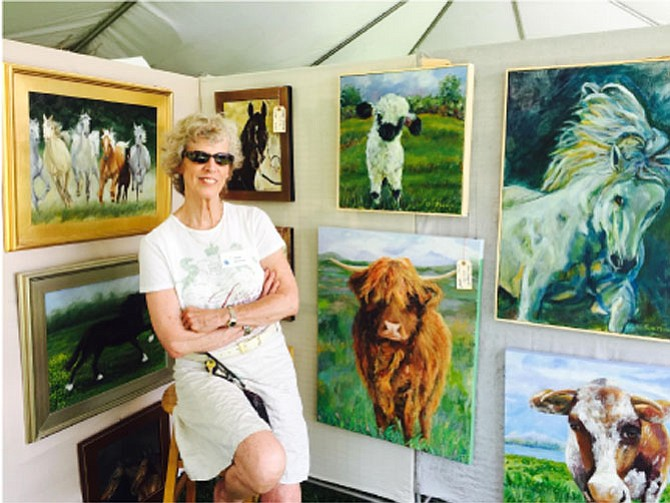 Artist Leslie Anthony poses with a few of her paintings for sale at last weekend's Great Falls Studios art show on the Village Green Centre.