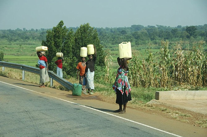 Women and children in Uganda carry heavy water jugs back to their villages.