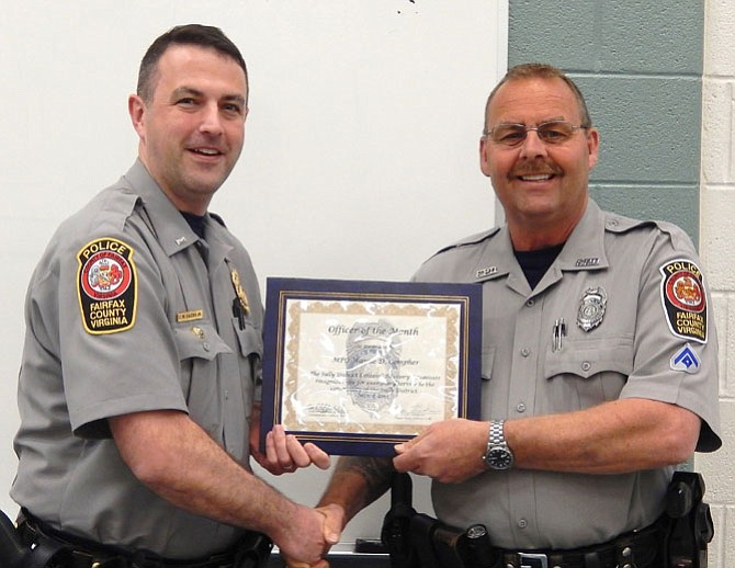 Lt. Matt Owens (left) presents an Officer of the Month certificate to MPO Wayne Compher.
