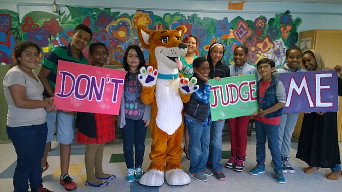 "DreamDog Foundation mascot Jazz poses for a photo with Kids Empowering Kids students at the premier of the ""Don't Judge Me"" music video June 11 at William Ramsey Elementary School. The students wrote, produced and starred in the video that aims to educate others about tolerance."
