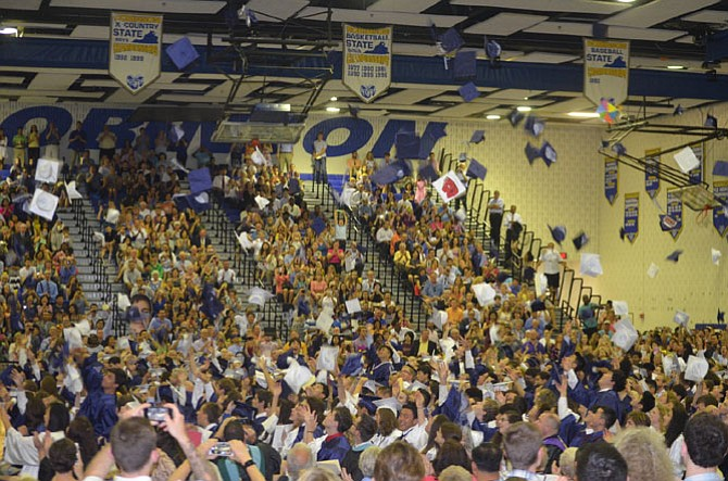 Woodson Class of 2015 toss their hats in celebration at the end of the ceremony.