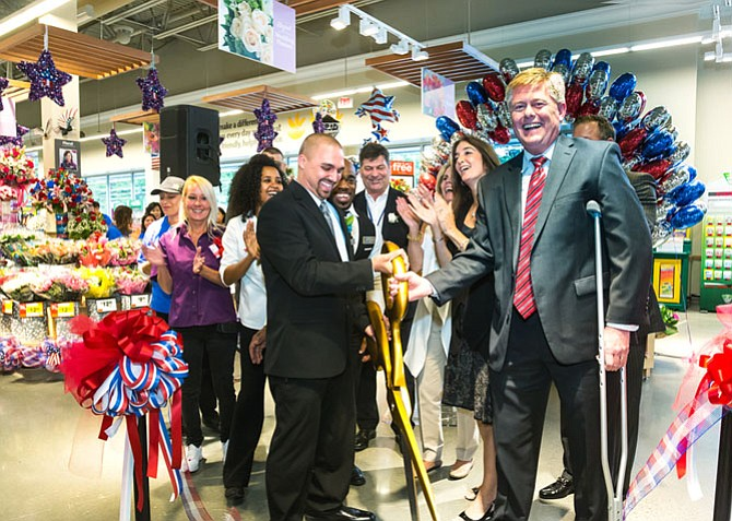 Store manager Scott Belcher (left) and supervisor John Cook (R-Braddock) cut the ribbon to officially open the new Giant Food grocery store at Kings Park Shopping Center.