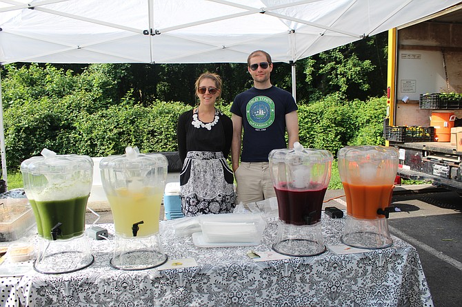 Lisa Marchand of Alexandria and Andrew Burr of Washington D.C. run the juice stand at the McLean Farmers Market on Friday mornings.