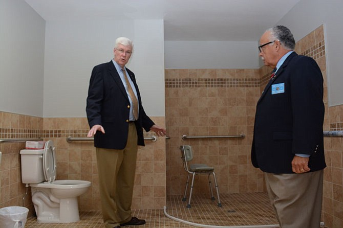 Marian Homes director William C Baker (left) and District 14 Warden for the Knights of Columbus Fidel Rodriguez tour one of the fully transformed bathrooms in the Queen of Peace house.