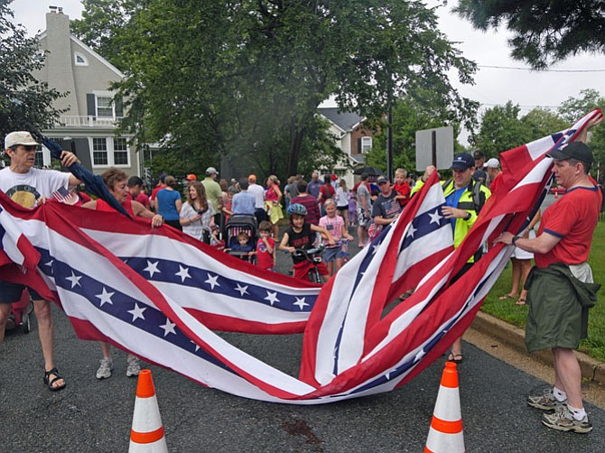 Doug and Lynne Ross and John Armstrong unfurl the street-wide flag that will signal to the red, white and blue sea of children that the Lyon Village Fourth of July parade is about to begin.