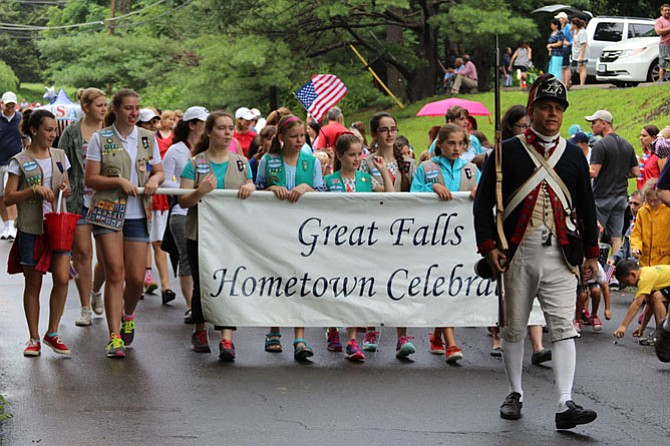 Mark Casso leads the parade with area Girl Scouts. Despite a 30-minute rain delay, hundreds of people participated in the festivities.