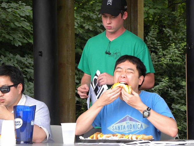 Paul Im, of Vienna, eats 10 chili dogs during a hotdog eating competition during the town of Vienna's Fourth of July festivities. He lost to Vienna resident Thomas Jung, who bested him by eating 11.