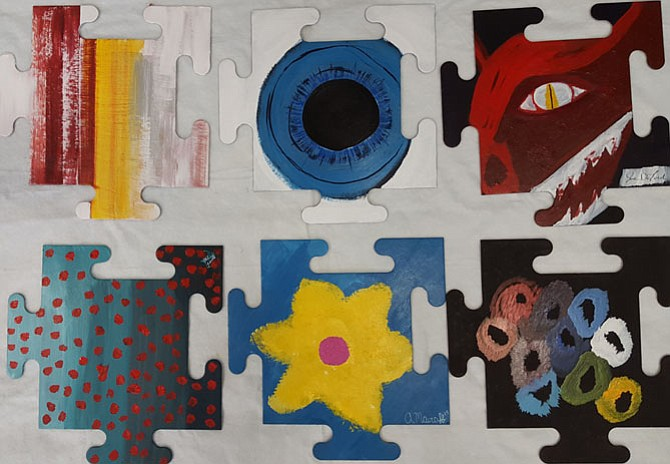 "Individual puzzle pieces, painted by soldiers suffering from PTSD, lay ready to be assembled by Vienna Arts Society volunteers into a giant collaborative work, on exhibit at the Vienna Arts Center. This is the second year VAS has produced the ""Healing Wall"" puzzle project."
