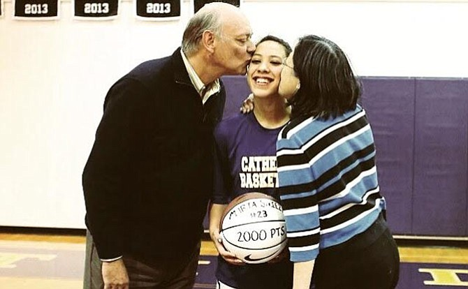 Marta Sniezek's father and mother, David and Edwina, kissing Marta as she is awarded a basketball for her 2,000 career point at the National Cathedral School.