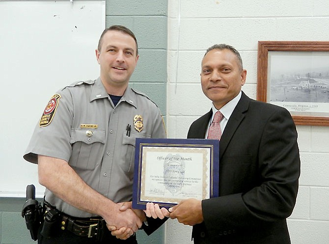 Police Lt. Matt Owens (left), the Sully District Station's assistant commander, presents the Officer of the Month award to APO Tony Gul.