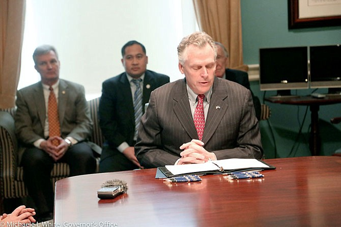 Photo of Virginia Governor Terry McAuliffe at the signing of the Transportation Network Company law (SB1025 and HB1662), signed in February. The law outlines regulations on vehicle registration and identification.