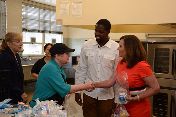 San Francisco 49ers wide receiver Torrey Smith (center) and First Lady of Virginia Dorothy McAuliffe (right) meet with some of the food preparation staff at Hollin Meadows Elementary School during a visit to the Summer Food Service Program.