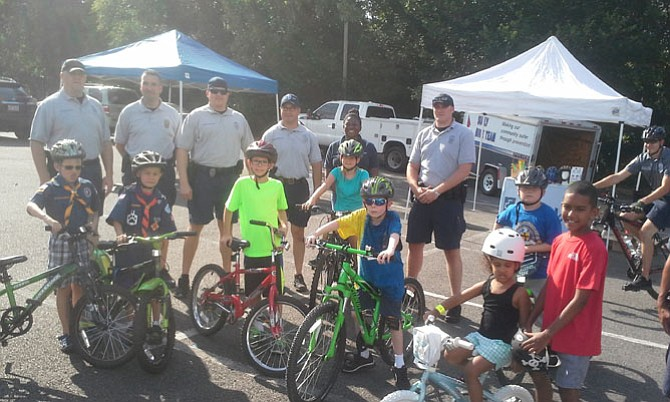 Fairfax County Police Officers, Linda Watkins from INOVA, and Cub Scouts with their siblings gather for a photo.