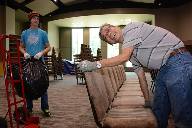 Rising South County senior and Christ Church member Patrick Richards (left) helps head custodian Phat Dang (right) set up chairs in the brand new 630-seat worship area.
