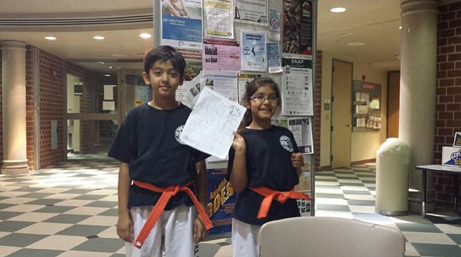 From left -- Akshat and Bhumi proudly display one of their summer reading logs.