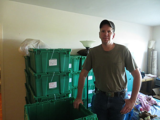 Greg Cain with the moving boxes in his family's Hunting Point apartment.