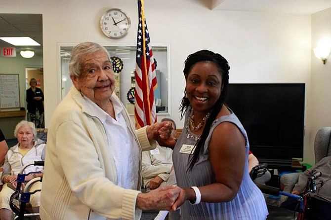 Margaret Estrada spends time with Afua Yankobah, an adult day health Care staff member at the Herndon Harbor Adult Day Health Care center.