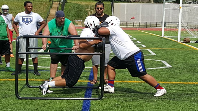 Wakefield rising senior linemen Anthony Tham, left, and Ryan Jones go through a drill during practice on Monday.