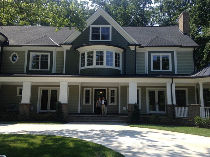 Tourette Syndrome Association of Greater Washington, D.C. Board member Tammy Starling and volunteer Michael Chow in front of the Home of Distinction at 8601 Nutmeg Court, Potomac. Through Aug. 9, the public is invited to tour this $3.9 million home to benefit the association.