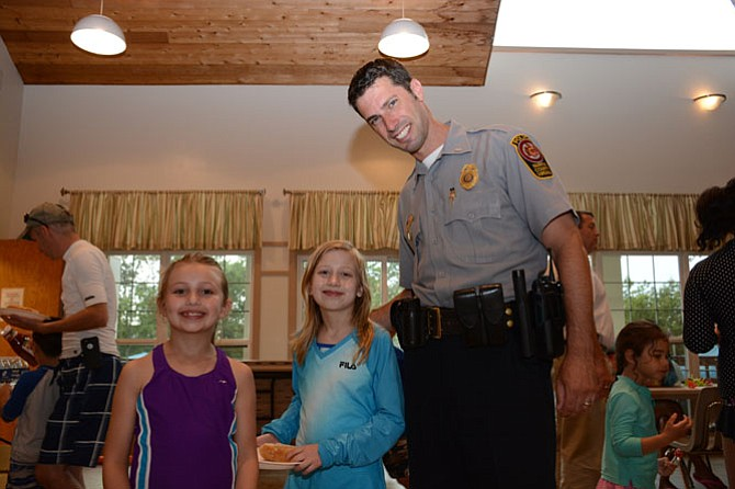 (From left) Katelyn and Elizabeth Stuebner meet with Lt. Eli Cory, assistant commander of the West Springfield district police station, before adding condiments to their hot dogs during National Night Out in Little Rocky Run.
