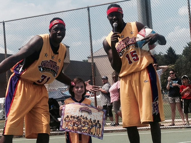 Tenley Schvimmer, 6, poses in her new prize jersey with Harlem Wizards John Smith and Lloyd Clinton