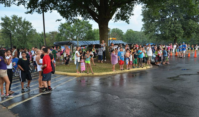 The crowds await the arrival of the motorcade bringing Herndon law enforcement personnel, town officials and volunteers to the last stop on the National Night Out 2015 route. The wait – and the rain drenching – were worth it, as the gathered neighbors were treated to goodies, a motorcycle handling performance and the arrival of a Fairfax County police helicopter for an up-close inspection.