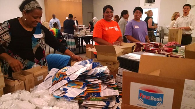 Representatives from The Reading Connection, First Book, Boeing and partner agencies stuff backpacks with a set of supplies and books.