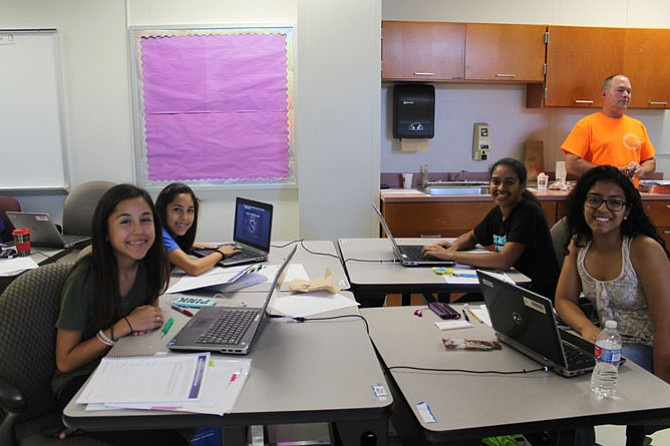 Rising eighth graders at Rachel Carson Middle School, Kinsey Clements (bottom left) and Kirsten Clements (top left) work with their partners, Monica Saraf (top right) from Nysmith middle school and Paola Henriquez (bottom right) from Chantilly High School to prepare for the mock cyberpatriot competition. More than half the camp attendees this year were girls.