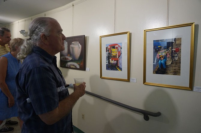 Artist Tom Kirby studies some of the entries on display at the Young At Art opening reception at the Durant Center Aug. 26.