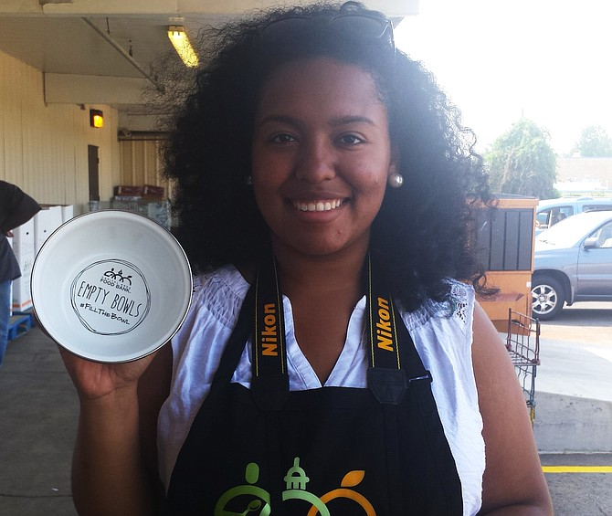 Ihamna Valencia, CAFB Visual Communications Coordinator, holds one of the enamelware bowls that will sold from Sept. 1 to Oct. 16 as part of CAFB's fundraising efforts. Businesses and individuals are invited to partake by purchasing bowls and spreading the word using the hashtag, #fillthebowl.