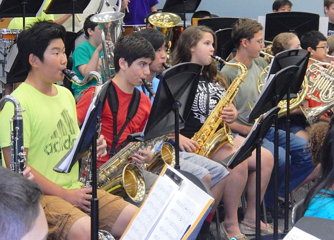 Students play saxophones and other brass instruments with the symphonic band.
