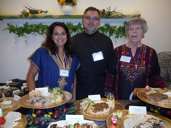 Holly Transfiguration Melkite Greek-Catholic Church volunteers Cathy Baroody, Proto Deacon David Baroody, and Mary Baroody arrange plates of Middle Eastern dishes available at the church's annual food festival.