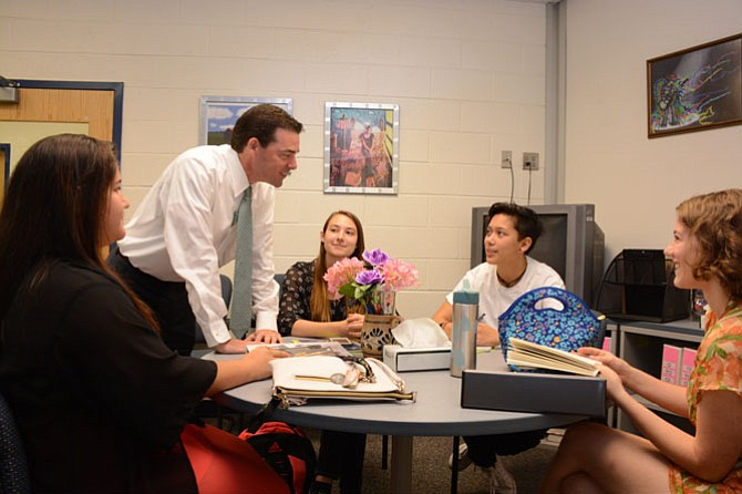 South County High School principal Matt Ragone looks at class schedules with students during the first day of school.