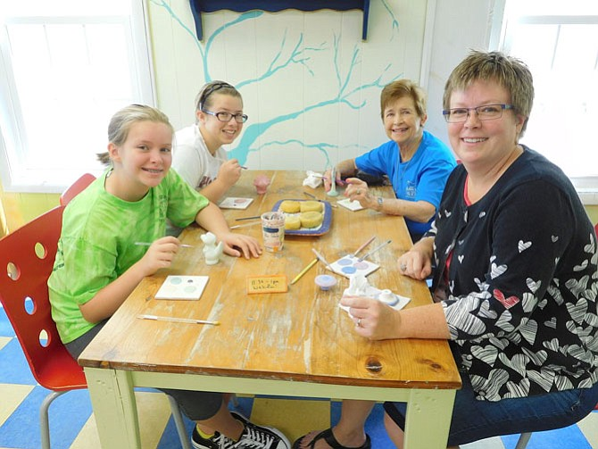 Having fun painting pottery together are (from left) sisters Kiara and Mikaela Fenn, grandmother Gloria Fenn and mom Molly Stephenson.