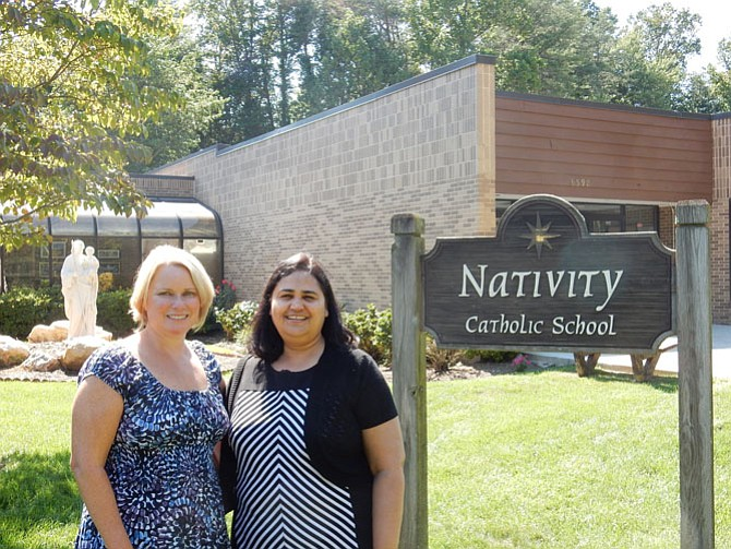"Maria Kelly, principal, and Annie Fernandez, assistant principal, in front of the entrance at Nativity Catholic School. They hope that their technology programs will help the students become ""active problem solving learners."""