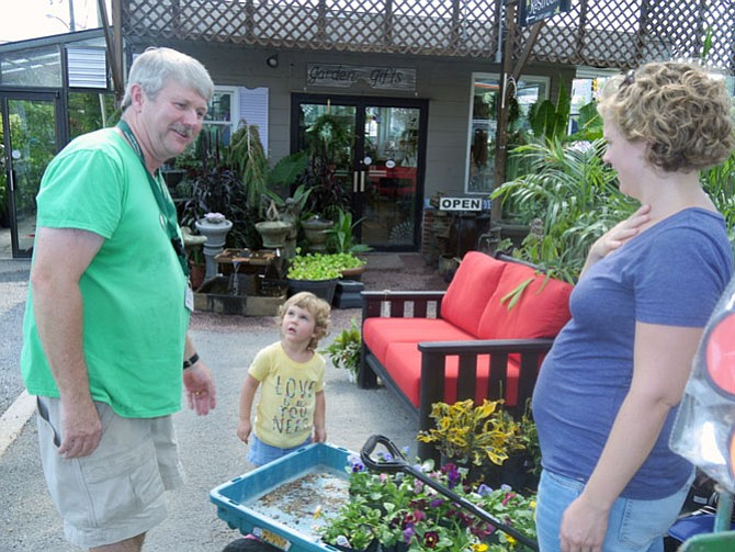 Kerry Sprinks and her daughter Daphne have filled a wagon full of pansies to put in planters for the fall season. Scott Sutherland tells her that if the pot is large enough they could go dormant and come back in the spring with even stronger roots.