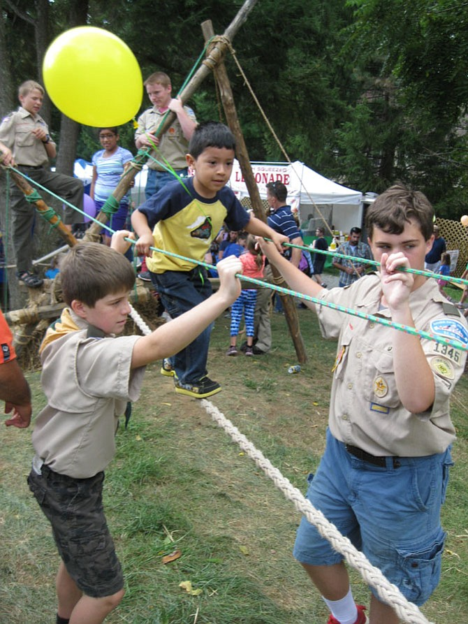 Walking across the Monkey Bridge at the 2015 Burke Centre Festival is Jean Pierre Portillo of Alexandria. The bridge was constructed by members of Boy Scout Troop 1345 of the Burke Centre Conservancy.