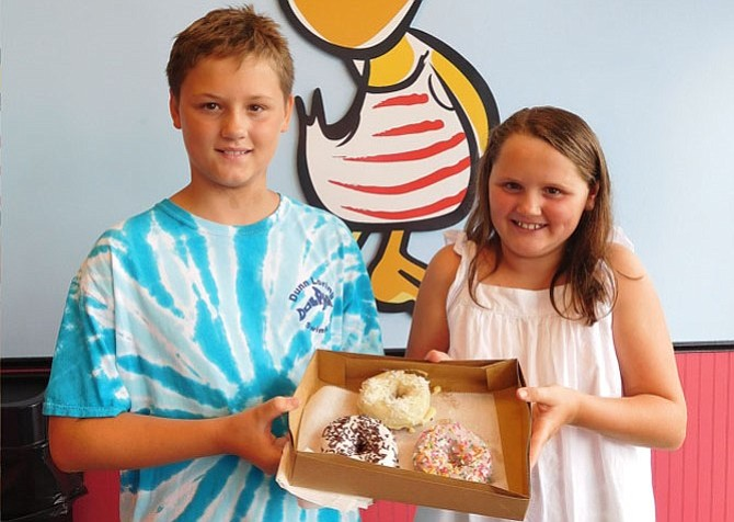 Siblings Bo and Emma Lewis show off their doughnuts – strawberry-frosted with rainbow sprinkles, vanilla with chocolate sprinkles and lemon with coconut.