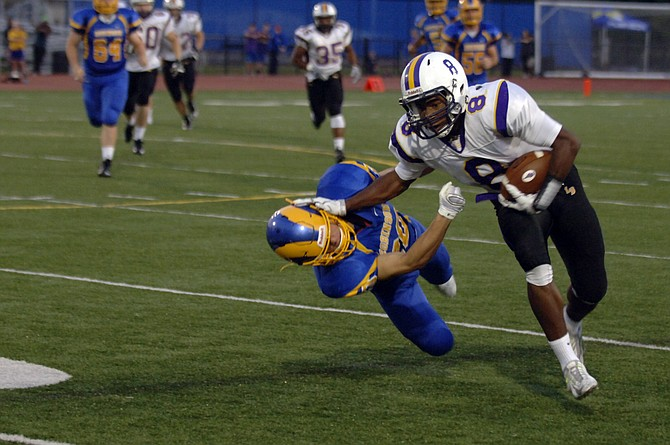 Lake Braddock running back Lamont Atkins stiff-arms a Robinson defender during the Bruins' 21-14 victory on Friday.